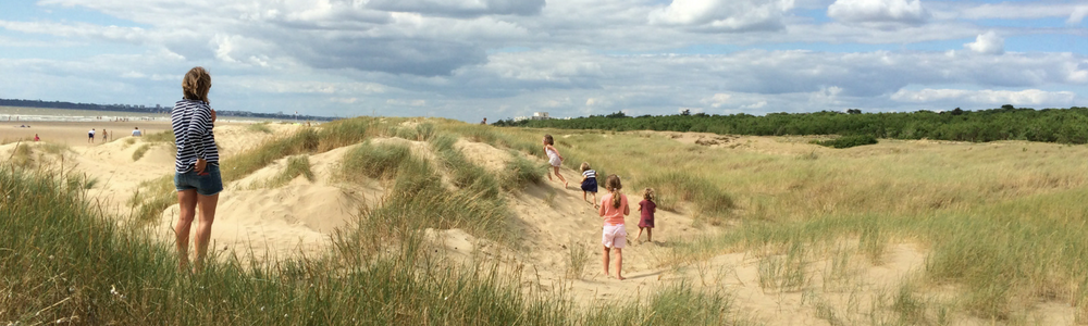 Family playing in sand dunes