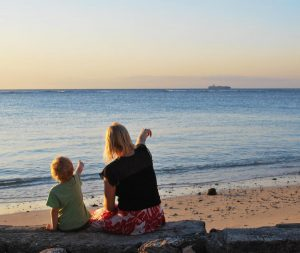 Mother and son looking at the sea and pointing at a ship in the distance