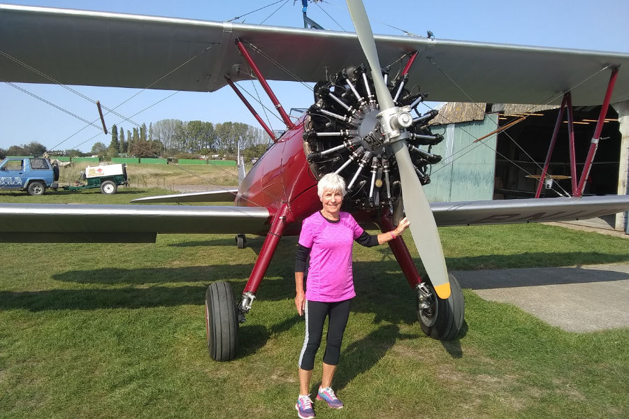 Supporter Christine standing next to a bi-plane