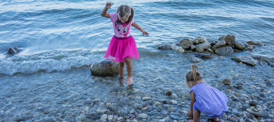 Children playing in the shoreline of a pebble beach