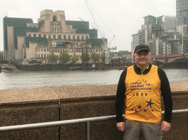 John de Vial wearing a bright yellow Family Holiday Association branded top in front of the River Thames