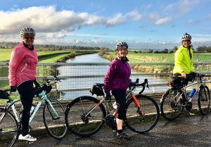 Philippa cycling with her cycling club along marshes in 2020
