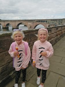 Two sisters stand next to a river. Both with a big smile on their face and an ice lolly in hand. In the background you can see an old stone built bridge.